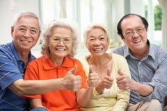 Grupp av höga kinesiska vänner som hemma kopplar av Royaltyfri Bild