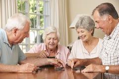 Grupp av höga par som hemma tycker om leken av domino Arkivfoto