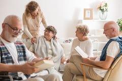 Grupp av höga vänner som tillsammans spenderar tid på vårdhemmet royaltyfria foton