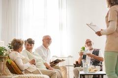 Grupp av höga vårdhempensionärer som tillsammans sitter på gemensam vardagsrum som lyssnar till den unga sjuksköterskan royaltyfri fotografi