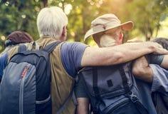 Grupp av höga vuxna människor som trekking i skogen royaltyfria foton