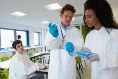 Grupp av högskolestudenter i vetenskapsgrupp med experiment arkivbild