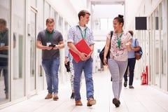 Grupp av högskolestudenter som promenerar korridoren royaltyfria foton
