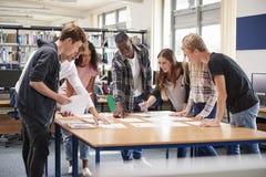Grupp av högskolestudenter som samarbetar på projekt i arkiv arkivbild