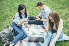 Grupp av högskolestudenter som sitter som använder utomhus mobiltelefoner arkivbild