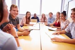 Grupp av högskolestudenter som sitter på tabellen som har diskussion arkivbild