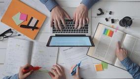 Grupp av högskolestudenter som studing Läseböcker som markerar information och använder bärbara datorn stock video