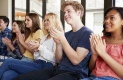 Grupp av högstadiumstudenter som applåderar presentation fotografering för bildbyråer