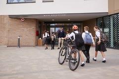 Grupp av högstadiumstudenter som bär enhetligt ankomma på skola som går eller rider cyklar som hälsas av läraren royaltyfri fotografi