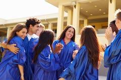 Grupp av högstadiumstudenter som firar avläggande av examen Arkivbild
