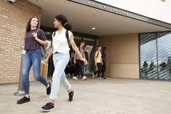 Grupp av högstadiumstudenter som går ut ur högskolan som tillsammans bygger royaltyfria foton