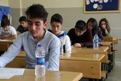 Grupp av högstadiumstudenter som tar ett prov i klassrum Royaltyfria Bilder
