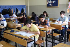 Grupp av högstadiumstudenter som tar ett prov i klassrum Royaltyfri Fotografi