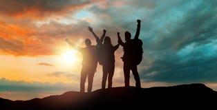Grupp av handelsresande med ryggsäckar över solnedgång royaltyfria foton