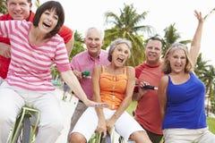 Grupp av höga vänner som har gyckel på cykelritt Royaltyfri Bild