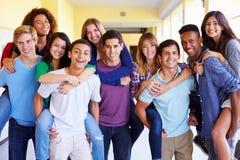 Grupp av högstadiumstudenter som ger ridturer på axlarna i korridor Arkivbilder
