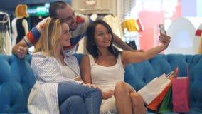 Grupp av hipsters i shoppinggallerian som tar selfie genom att använda den smarta telefonen Fotografering för Bildbyråer