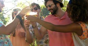 Grupp av hipstervänner som rostar med exponeringsglas av öl lager videofilmer