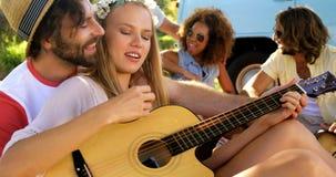 Grupp av hipstervänner som spelar musik tillsammans lager videofilmer