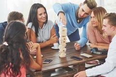Grupp av idérika vänner som sitter på trätabellen Folk som har gyckel, medan spela brädeleken royaltyfri fotografi