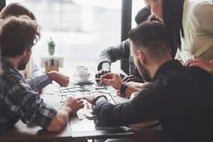 Grupp av idérika vänner som sitter på trätabellen Folk som har gyckel, medan spela brädeleken arkivfoton