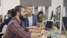Grupp av idérikt folk som arbetar med datoren arkivfilmer
