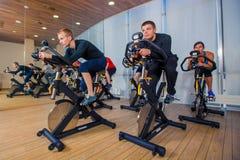 Grupp av idrottshallfolk på maskiner som cyklar i grupp Fotografering för Bildbyråer