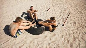 Grupp av idrottsman nen som gör crossfitövningsrutin på stranden arkivbild