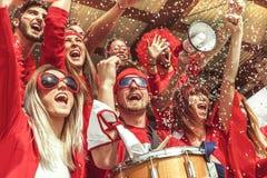 Grupp av iklädd röd färg för fans som håller ögonen på en sporthändelse royaltyfri fotografi