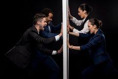 Grupp av ilskna affärsmän som är klara att slåss med affärskvinnor från den avskilda väggen Royaltyfri Bild