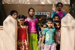 Grupp av indiska fattiga ungar med modern som ser kameran 11 februari 2018 Puttaparthi, Indien Arkivfoton
