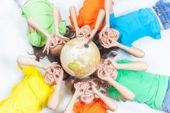 Grupp av internationella roliga ungar med jordklotjord arkivfoton