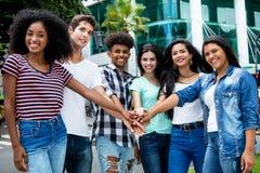 Grupp av internationellt ungt vuxet folk som bygger ett lag royaltyfri bild