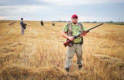 Grupp av jägare med vapen som flyttar sig till och med fältet Fotografering för Bildbyråer