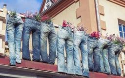 Grupp av jeans som används som blomkrukor Arkivfoto