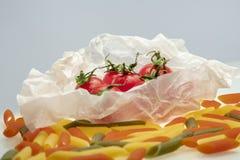 Grupp av körsbärsröda tomater som slås in, i att laga mat papper royaltyfria foton