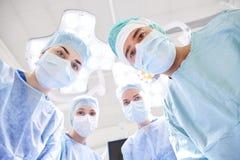 Grupp av kirurger i fungeringsrum på sjukhuset Arkivfoton
