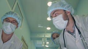 Grupp av kirurger som ner ser på patienten på vägen till operationrum arkivfilmer