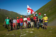 Grupp av klättrare i den gröna dalen för berg med flaggan av Georgia Royaltyfri Bild