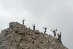 Grupp av klättrare som står på ett ojämnt bergmaximum och vinkar deras händer i luften royaltyfri bild