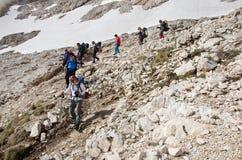 Grupp av klättrare som stiger ned från toppmöte Royaltyfria Bilder