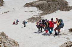 Grupp av klättrare som stiger ned från toppmöte Arkivbilder