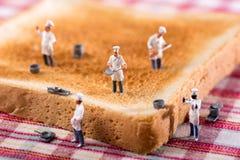 Grupp av kockar eller kockar på en skiva av vitt rostat bröd arkivbild