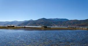 Grupp av kojor bredvid sjön Royaltyfri Bild