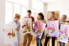 Grupp av konstnärer med bilder på konstskolan arkivfoton