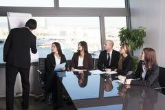 Grupp av kontorsarbetare i en styrelsepresentation Arkivfoto