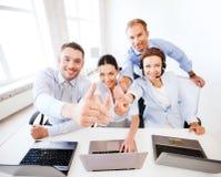 Grupp av kontorsarbetare som visar upp tummar Fotografering för Bildbyråer