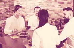 Grupp av kraftiga vänner som äter på restaurangen och att prata Fotografering för Bildbyråer
