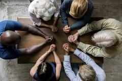 Grupp av kristendomenfolk som tillsammans ber hopp royaltyfri fotografi