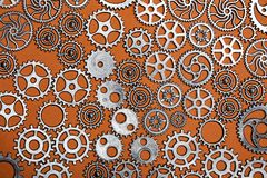 Grupp av kugghjul på en orange bakgrund Arkivbilder